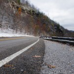 Snow falling along the mountain road.